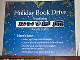 A Holiday Book Drive sign encourages donations to KNTR.