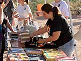 Volunteers arrange free books for the kids, provided by Changing Hands Bookstore.